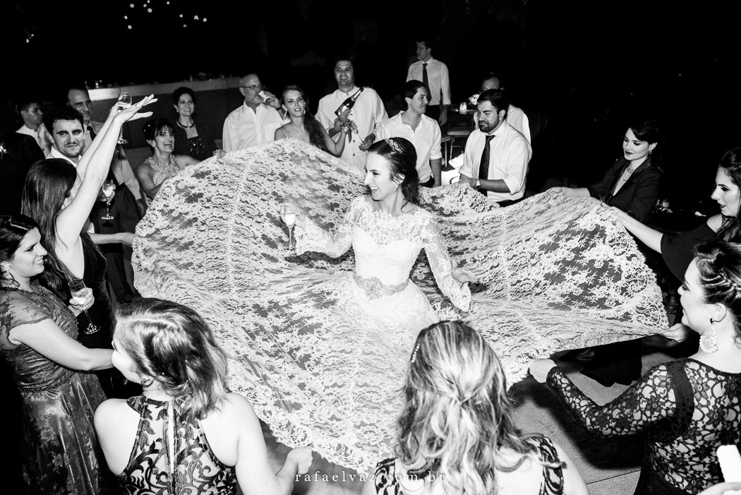 Noiva dançando no centro de uma roda e as amigas ao redor balançando a calda do seu vestido.