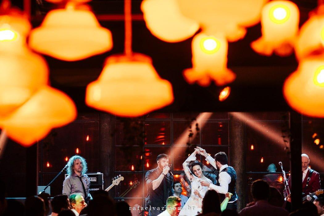 Noivos dançando no palco com a banda e várias luzinhas